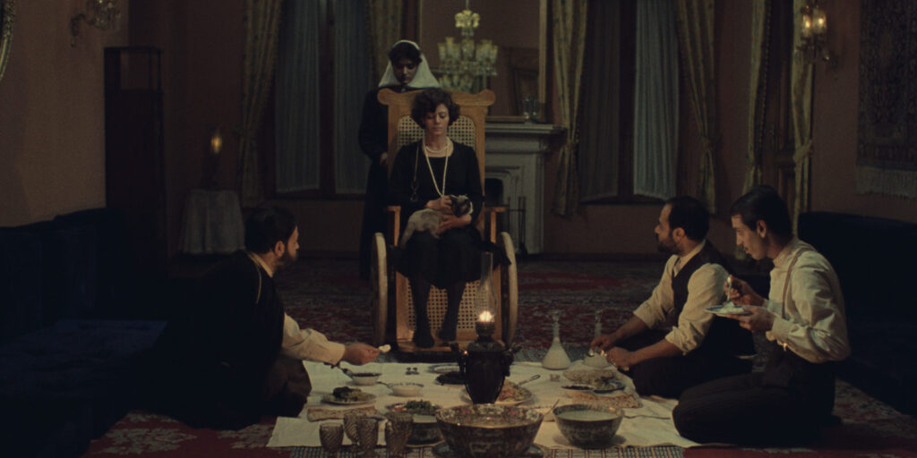 """A still image from the 1976 film """"Chess Game of the Wind"""" (""""Shatranj-e baad"""", featuring several actors congregating around a low-lit dinner spread"""