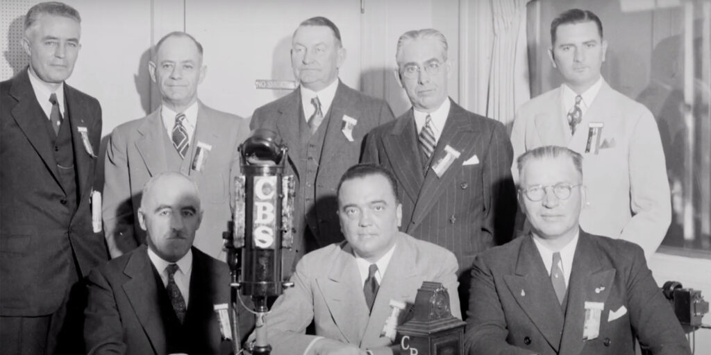 J. Edgar Hoover seated at a press conference surrounded by group of men