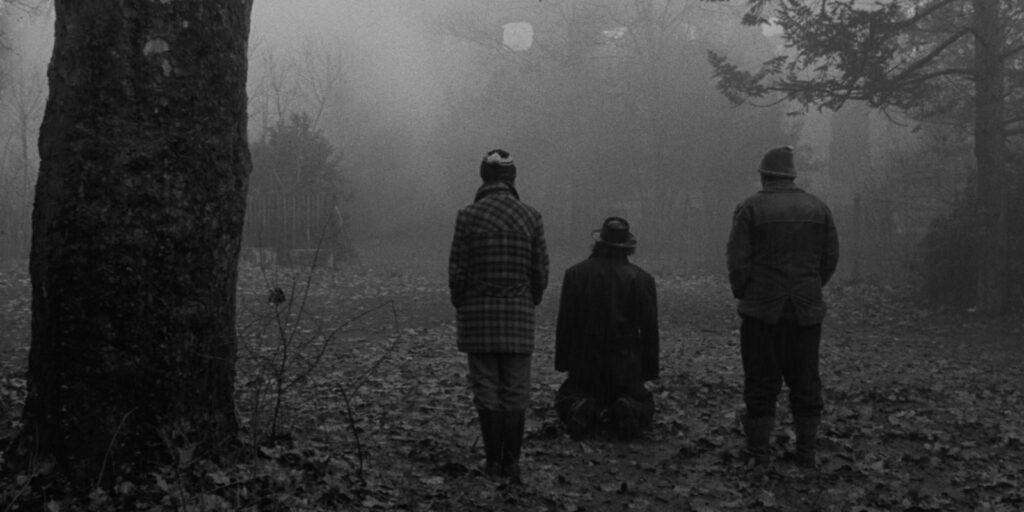 """A still image from the 1994 film """"Sátántangó"""" featuring three characters standing in a misty open grove"""