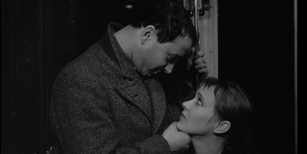 """A still image from the 1964 film """"Band of Outsiders"""", featuring actors Sami Frey and Anna Karina seated in a subway car"""
