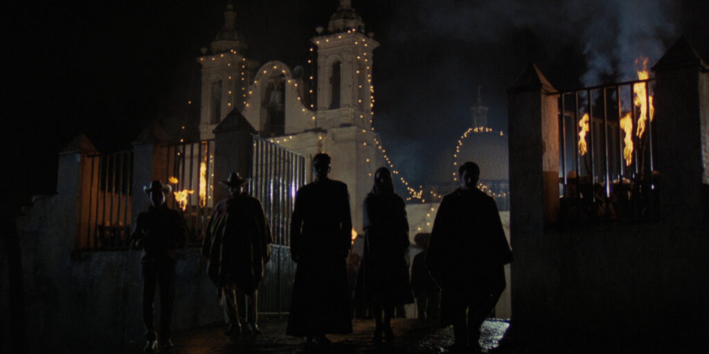 """A still image from the 1976 film """"Canoa: A Shameful Memory"""", featuring several actors standing outside of a church at nighttime"""