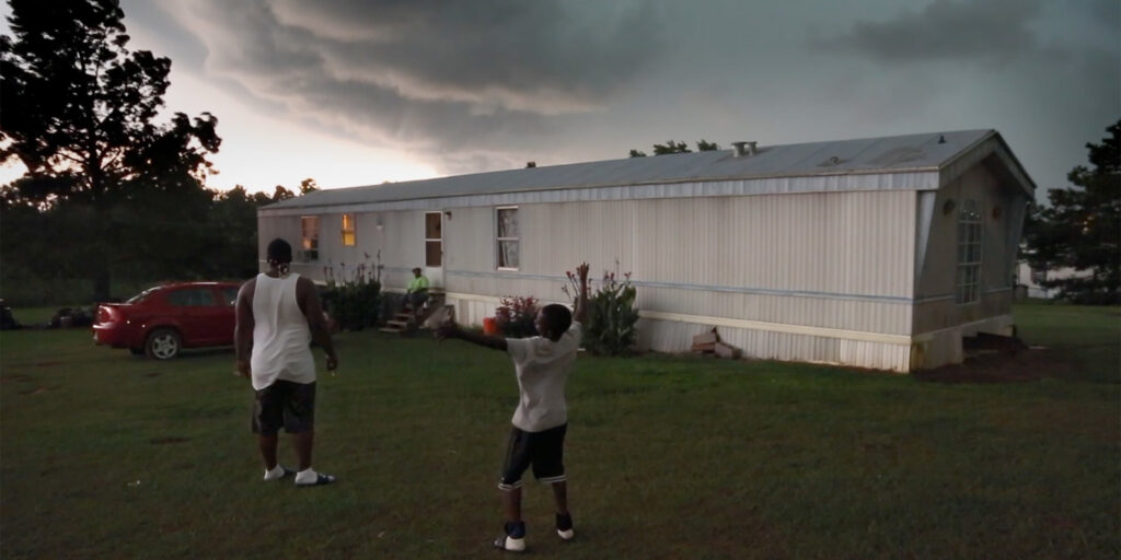 """A still image from the 2018 documentary """"Hale County, This Morning, This Evening"""", featuring two people standing outside of their home as dark clouds approach from afar"""