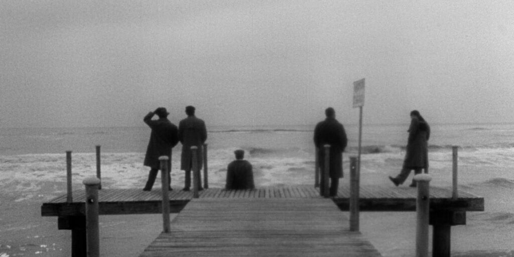 """A still image from the 1953 film """"I Vitelloni"""" of several characters standing on a dock"""