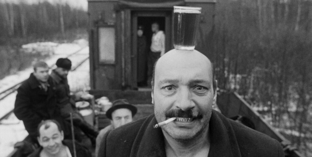"""A still image from the 1998 film """"Khrustalyov, My Car!"""", featuring actor Yuri Tsurilo balancing a drink on his head in front of other figures in an open-air train car"""