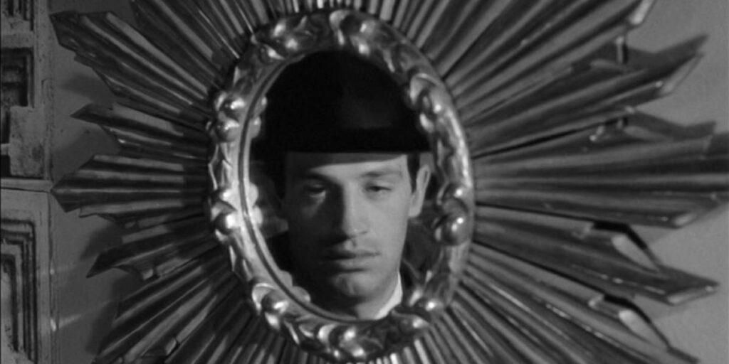 """A still image from the 1962 film """"Le Doulos"""", featuring actor Jean-Paul Belmondo staring in a mirror"""