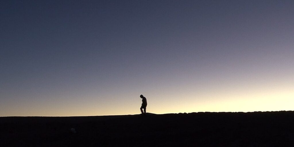 """A still image from the 2010 documentary """"Nostalgia for the Light"""", featuring a lone figure walking along a sandy hill at sunset"""