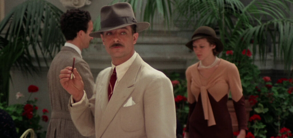 """A still image from the 1975 film """"Seven Beauties"""", featuring actor Giancarlo Giannini walking between two people and holding a cigarette"""
