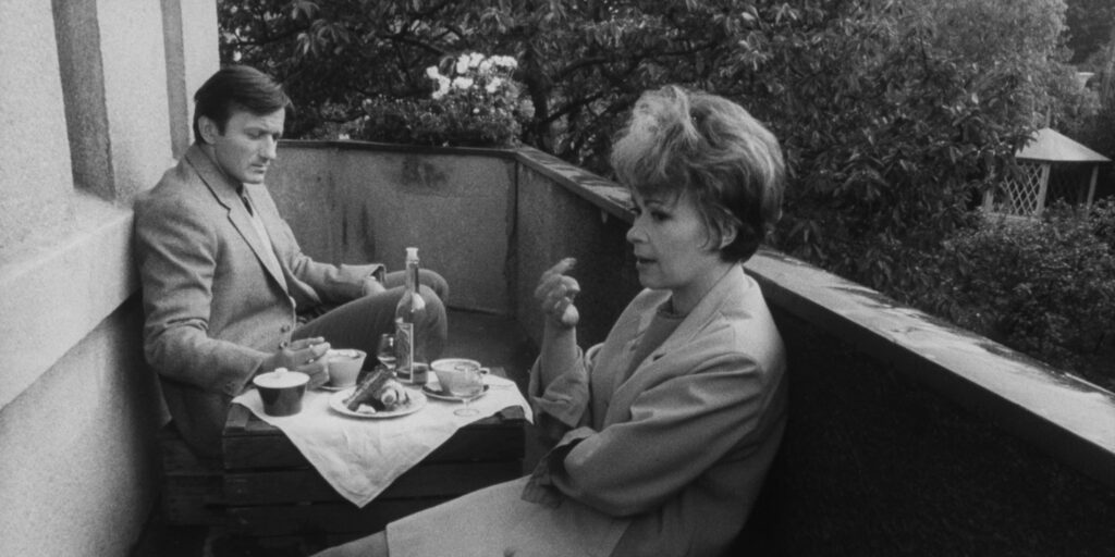 """A still image from the 1970 film """"The Ear"""" featuring actors Radoslav Brzobohatý and Jiřina Bohdalová seated on a balcony"""