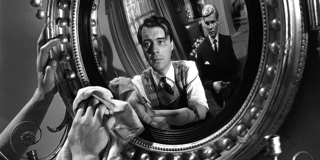 """A still from the 1963 film """"The Servant"""", featuring actors Dirk Bogarde and James Fox standing in front of a mirror"""