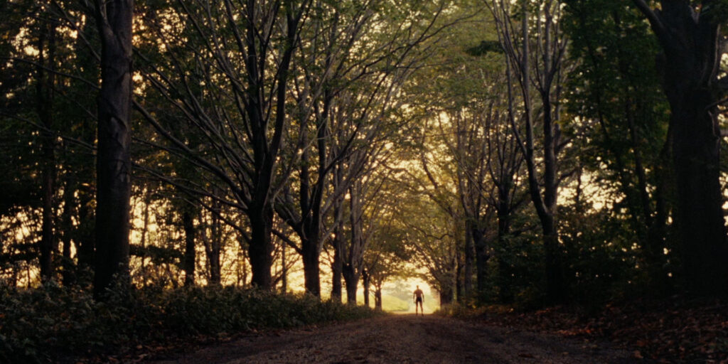 """A still image from the 1968 film """"The Swimmer"""", featuring Burt Lancaster walking in the distance along a wooded path"""