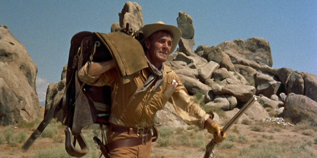 """A still image from the 1957 film """"The Tall T"""", featuring actor Randolph Scott trudging through the desert with his saddle bag slung over his arm"""