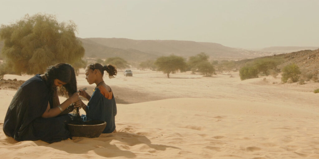 """A still image from the 2014 film """"Timbuktu"""" featuring actors Toulou Kiki and Layla Walet Mohamed seated in the desert"""