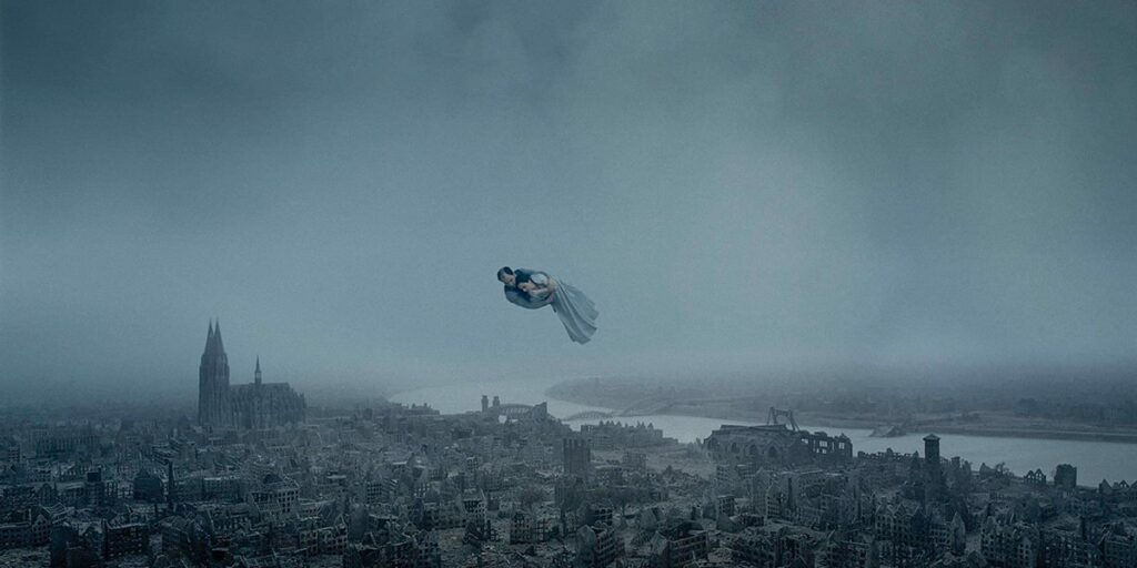 """A still image from the film """"About Endlessness"""" featuring a couple floating above a European city"""