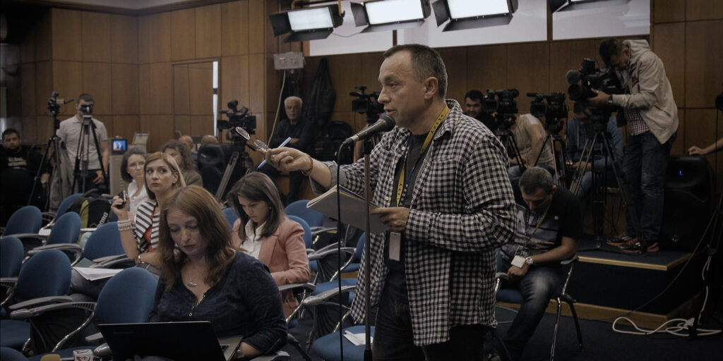 """A still from the documentary feature """"Collective"""" featuring journalist Cătălin Tolontan asking a question at a press conference"""