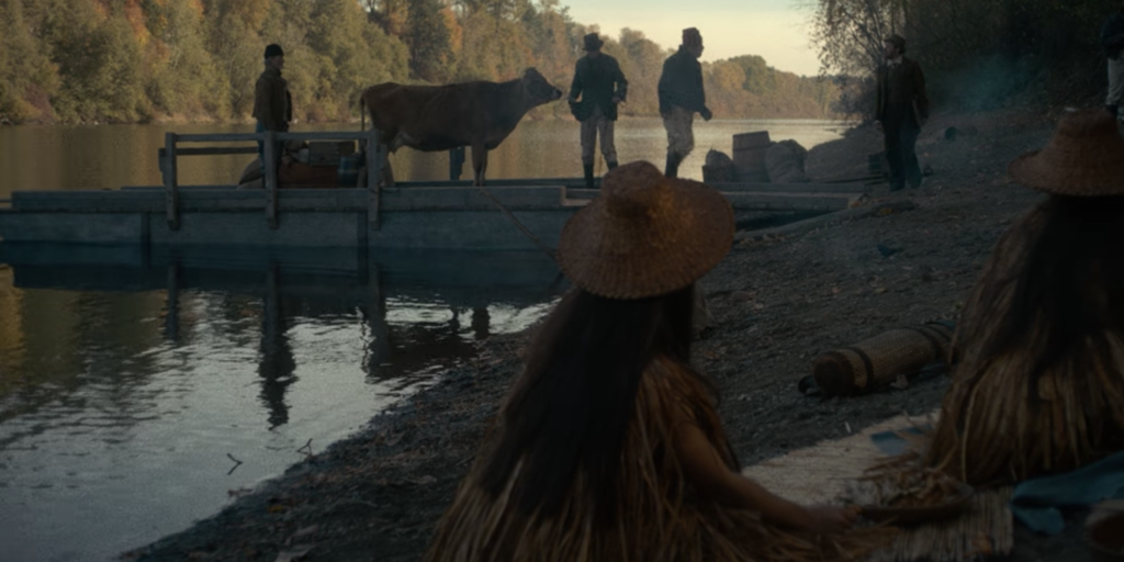 """A still image from the film """"First Cow"""", featuring settlers docking with a cow as indigenous peoples observe"""