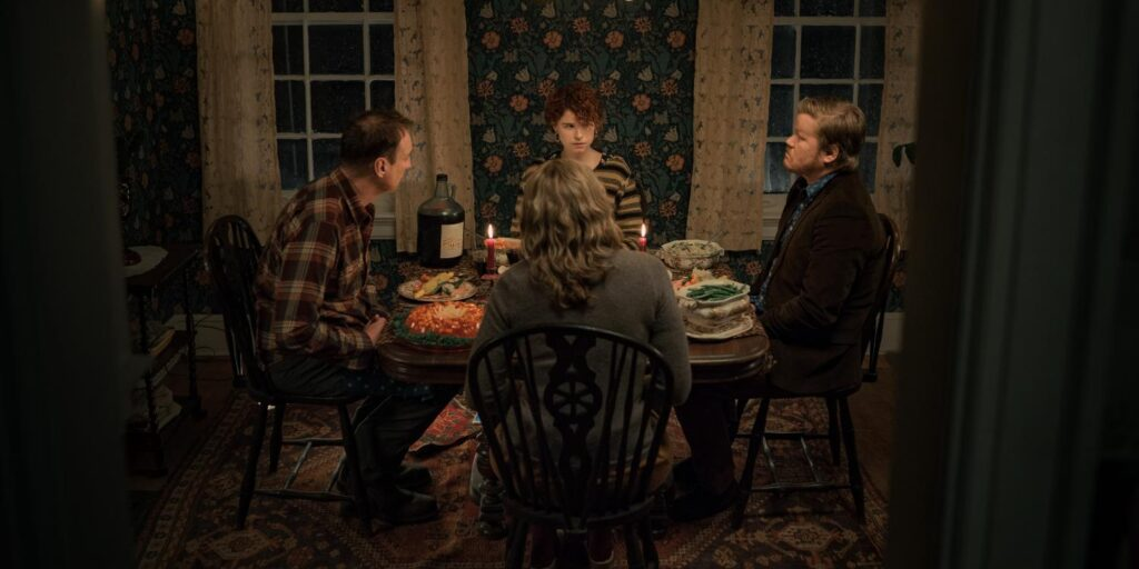 """A still image from the film """"I'm Thinking of Ending Things"""", featuring actors Jessie Buckley, Toni Collette, David Thewlis and Jesse Plemons all seated around a dining room table"""