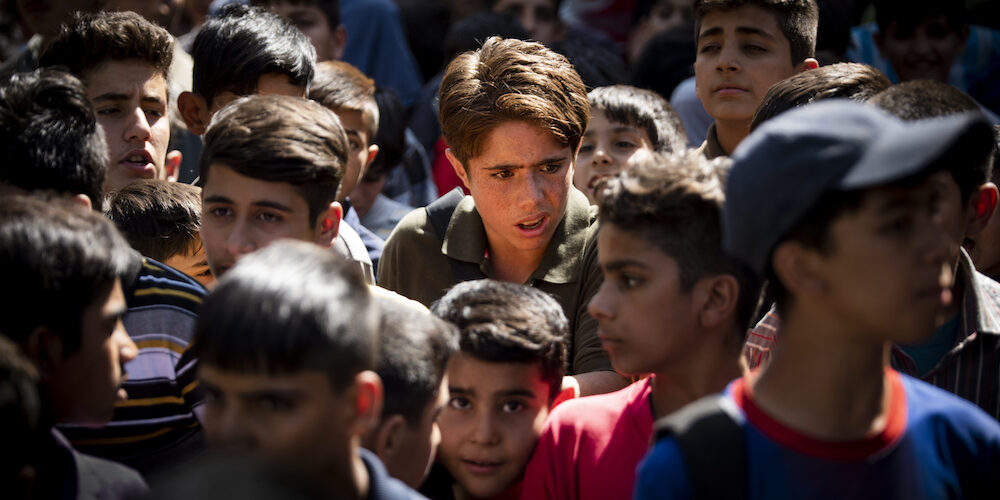 """A production still from the film """"Sun Children"""" featuring actor Roohollah Zamani standing amidst a crowd of boys"""