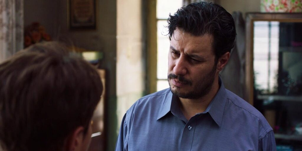 """A still image from the film """"Sun Children"""" featuring actor Javad Ezati staring intently at a student"""