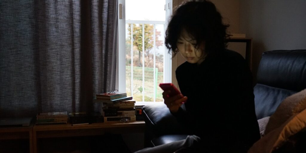 """A still image from the film """"The Woman Who Ran"""", featuring actor Kim Min-hee checking her phone in a dimly lit room"""