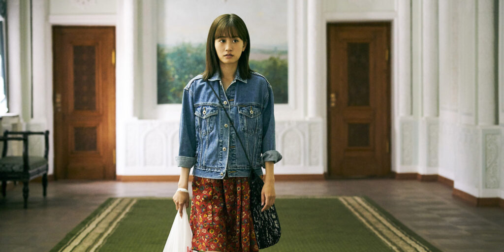 """A still image from the film """"To the Ends of the Earth"""" featuring actor Atsuko Maeda wandering a room in the Navoi Theater"""